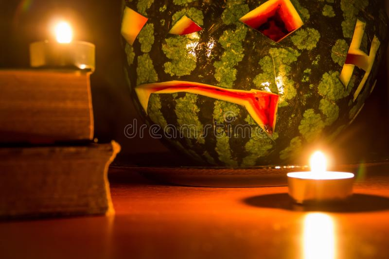 Halloween symbol, water-melon with carved red smiling face and burning candles on dark background stock photos