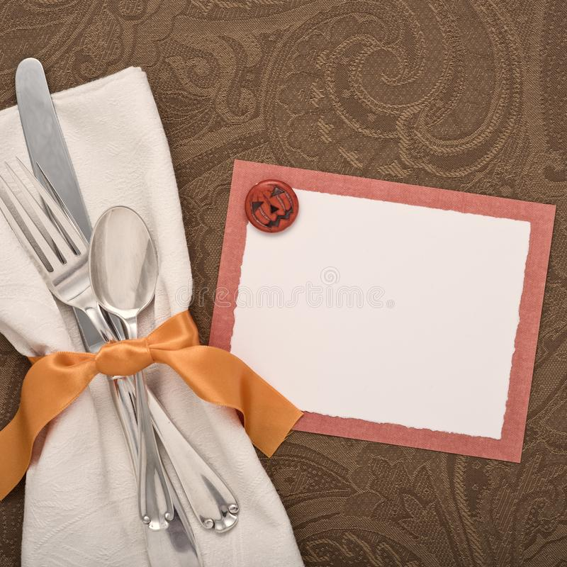 Halloween Table Place Setting with Silverware and Blank Card for your words, text or copy. Square crop with brown table cloth, wh stock photography