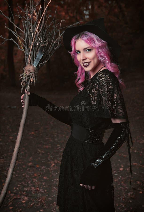 Halloween-Thema: zeitgenössische lächelnde junge Hexe im schwarzen Kleid und im Hut mit Besen im dunklen Wald lizenzfreies stockfoto