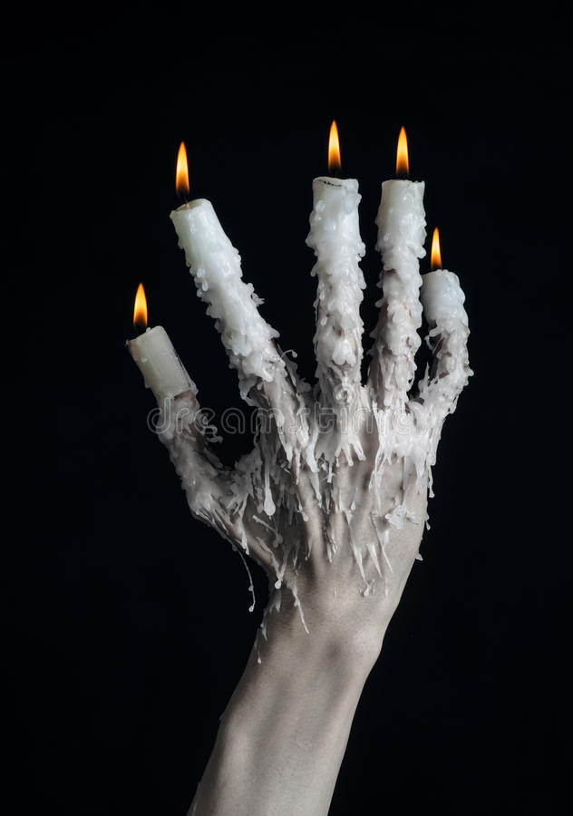 Halloween theme: on the hand wearing a candle and dripping melted wax on black isolated background. Studio royalty free stock image