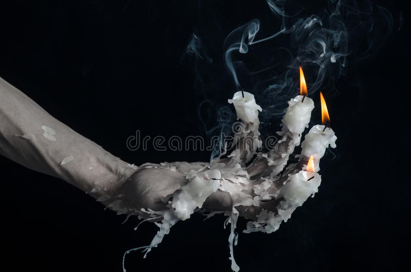 Halloween theme: on the hand wearing a candle and dripping melted wax on black isolated background. Studio stock photos