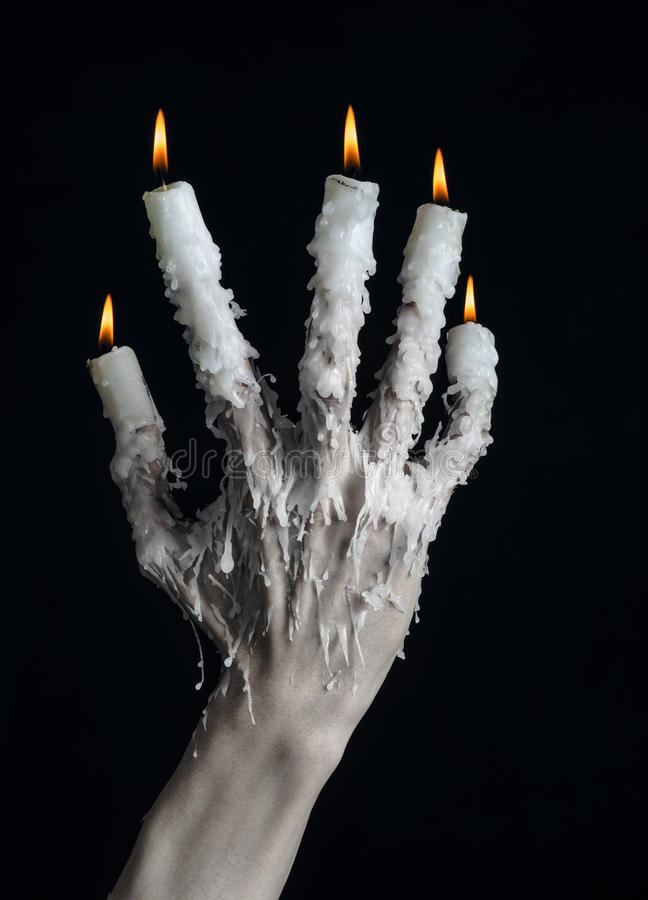 Halloween theme: on the hand wearing a candle and dripping melted wax on black isolated background. Studio royalty free stock photography