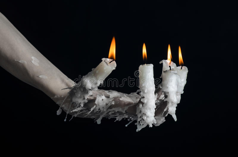 Halloween theme: on the hand wearing a candle and dripping melted wax on black isolated background. Studio stock images