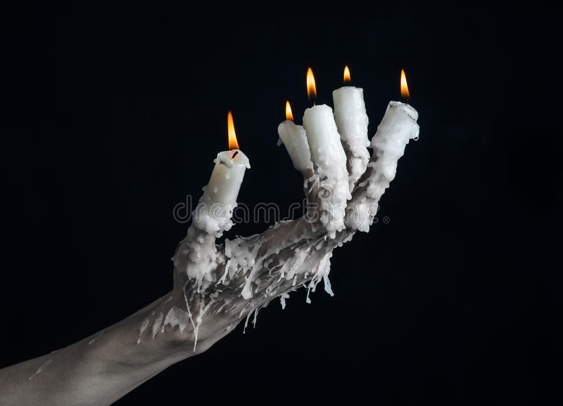 Halloween theme: on the hand wearing a candle and dripping melted wax on black isolated background. Studio royalty free stock photo