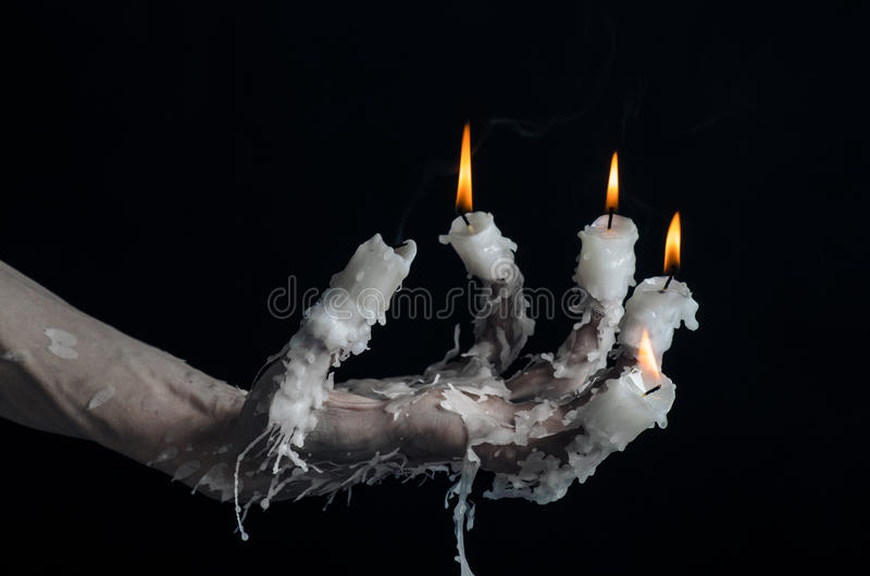 Halloween theme: on the hand wearing a candle and dripping melted wax on black isolated background. Studio stock photography
