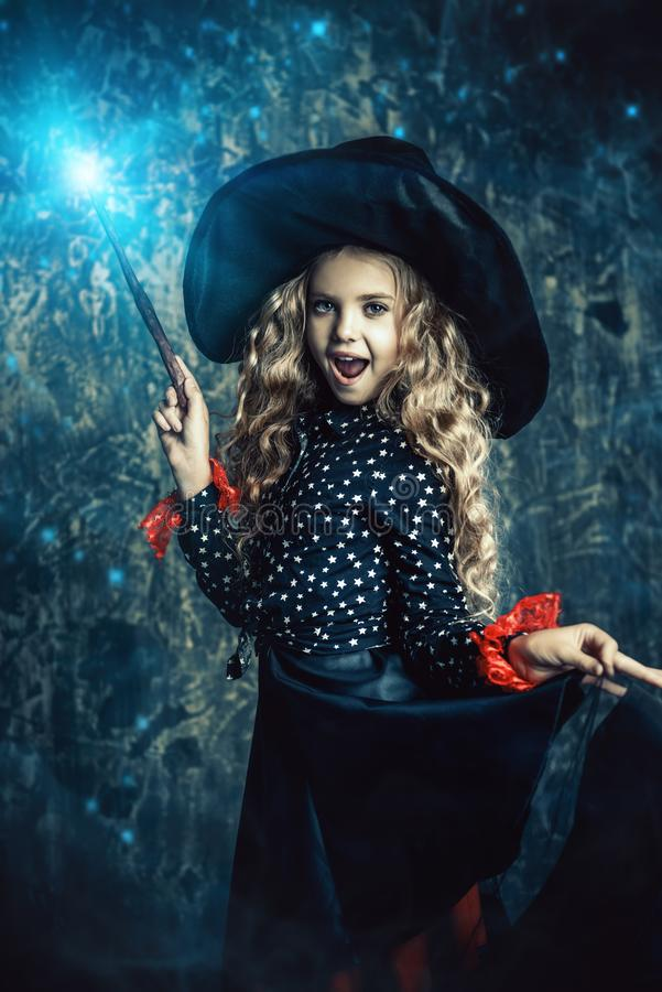 Halloween time and witch. Beautiful child girl in a costume of a witch over grunge background. Halloween party stock images