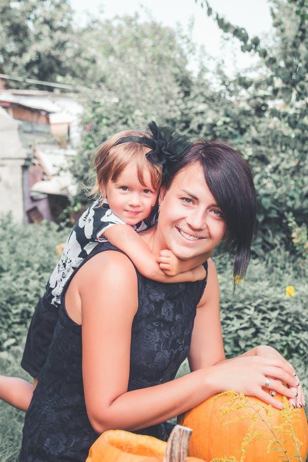 Halloween Tochter, die Mutter nahe Steckfassung-Olaterne im Garten umarmt Dekoration für Partei Glückliche Familie Getontes Foto stockfotos