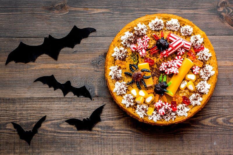 Halloween-Tradition Kürbiskuchen, Kürbis mit geschnitztem Gesicht und Schläger auf Draufsicht des hölzernen Hintergrundes lizenzfreies stockfoto