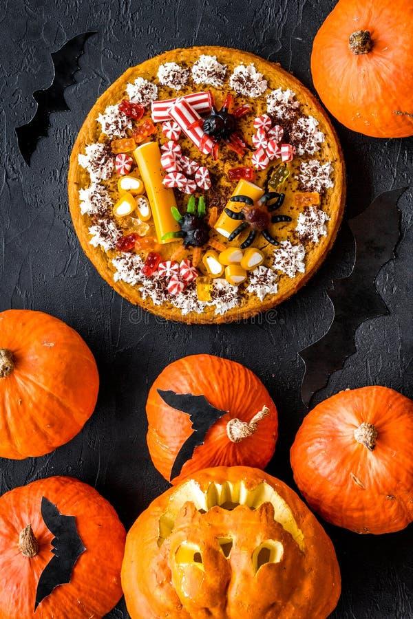 Halloween-Tradition Kürbiskuchen, Kürbis mit geschnitztem Gesicht und Schläger auf Draufsicht des schwarzen Hintergrundes stockbild