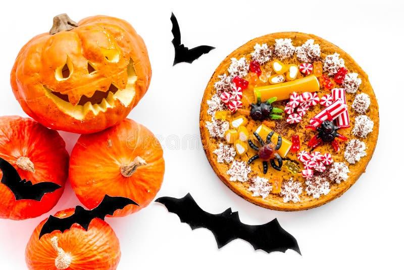 Halloween-Tradition Kürbiskuchen, Kürbis mit geschnitztem Gesicht und Schläger auf Draufsicht des weißen Hintergrundes lizenzfreie stockfotos
