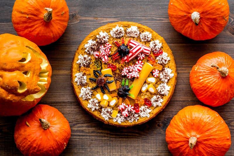 Halloween-Tradition Kürbiskuchen und Kürbis mit furchtsamem Gesicht auf Draufsicht des hölzernen Hintergrundes stockbild