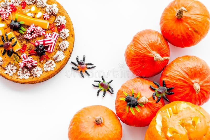 Halloween-Tradition Kürbiskuchen und Kürbis mit furchtsamem Gesicht auf Draufsicht des weißen Hintergrundes stockfotografie