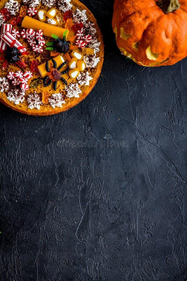 Halloween-Tradition Kürbiskuchen und Kürbis mit furchtsamem Gesicht auf schwarzem copyspace Draufsicht des Hintergrundes lizenzfreie stockfotografie