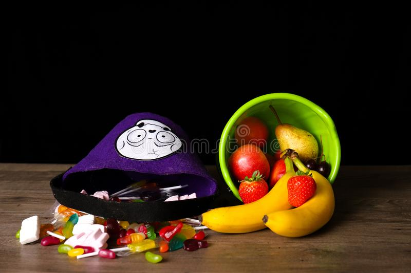 Halloween treats coming out of a bucket next to fruit coming out of another bucket. Unhealthy versus healthy concept royalty free stock photo
