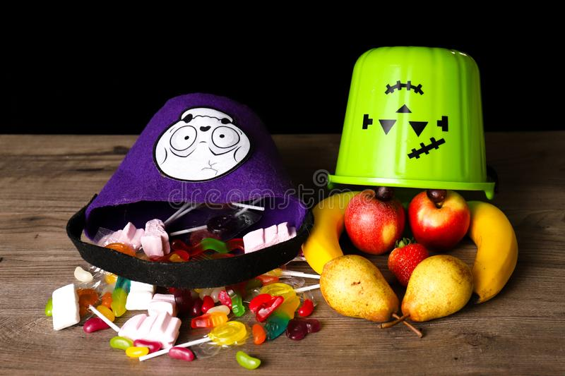 Halloween treats coming out of a bucket next to fruit coming out of another bucket. Unhealthy versus healthy concept royalty free stock images