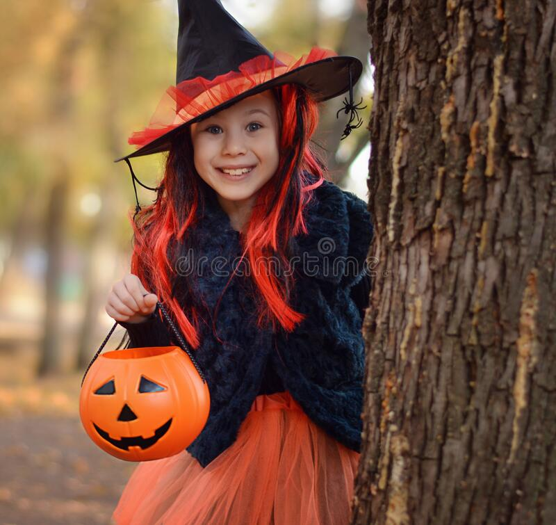 Free Halloween Trick Or Treat.Happy Girl Wearing A Witch`s Hat, With A Pumpkin Handbag, Peeps Out From Behind A Tree.. Funny Kid In Royalty Free Stock Image - 198486706
