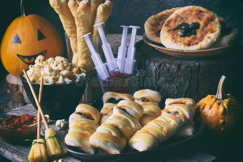 Halloween trick or treat party. Funny delicious food and pumpkin on wooden background - mini pizza, bread sticks, cheese, olives,. Ketchup, popcorn, juice. Copy royalty free stock photos