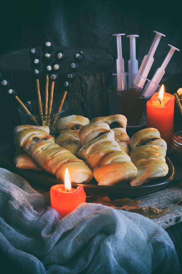 Halloween trick or treat party. Funny delicious food and pumpkin on wooden background - mini pizza, bread sticks, cheese, olives, stock image