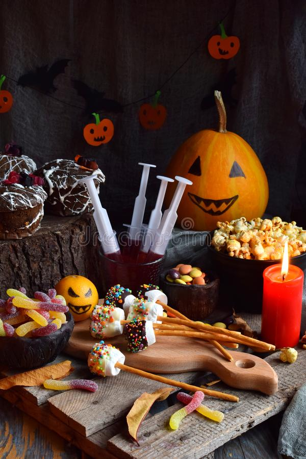 Halloween trick or treat party. Funny delicious sweets and pumpkin on wooden background - muffins, cupcakes, marshmallows, popcorn royalty free stock photos