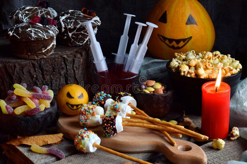 Halloween trick or treat party. Funny delicious sweets and pumpkin on wooden background - muffins, cupcakes, marshmallows, popcorn royalty free stock images