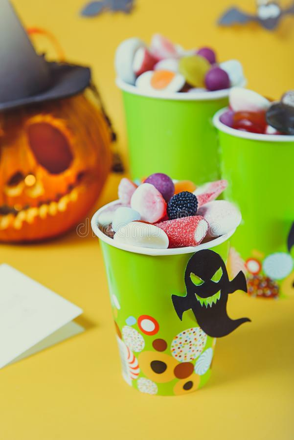 Halloween trick or treat sweets. Paper cups with colourful candies inside and paper silhouettes of bats, ghosts, witch on bright royalty free stock images