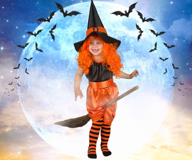 Little girl witch flying on a broom across the sky. royalty free stock images