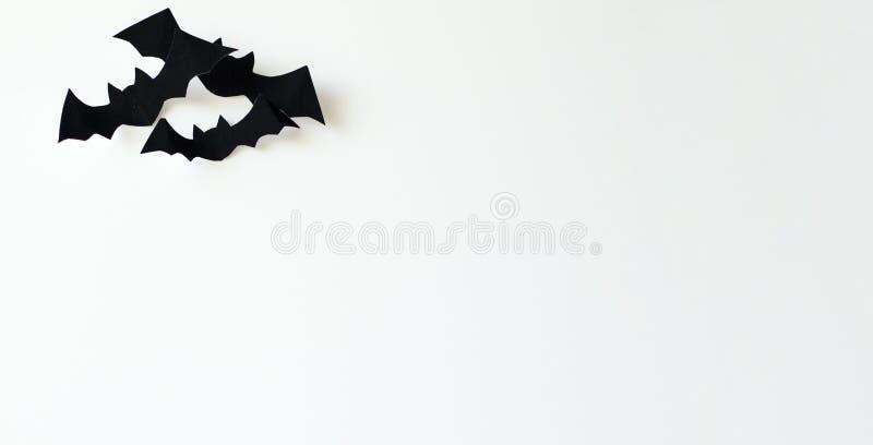 Halloween und Verzierungskonzept - schwarze Papierschläger machten von der Samtpapierfliege über einem weißen Hintergrund stockbild