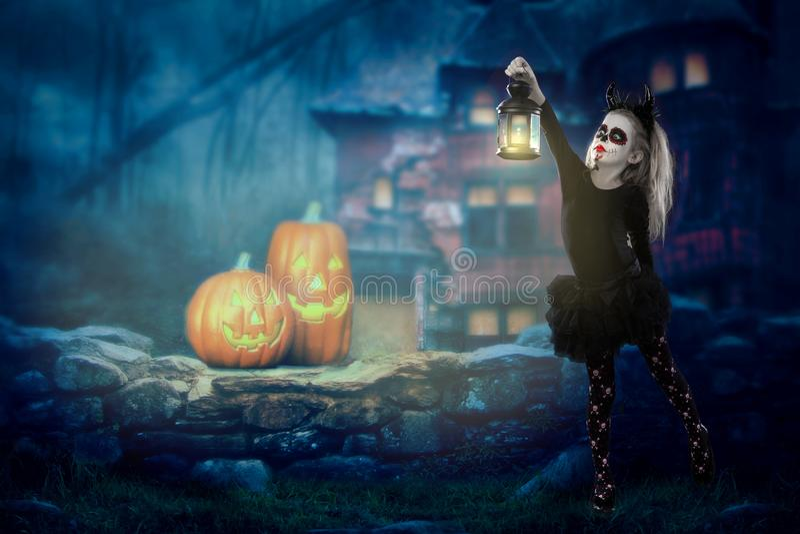 Halloween, vacances, concept de mascarade - le portrait de la jeune petite belle fille avec le maquillage de crâne sur le fond de photo libre de droits