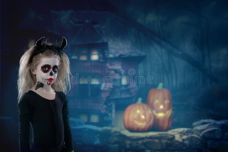 Halloween, vakantie, maskeradeconcept - het portret van jongelui weinig mooi meisje met schedelmake-up en hoornen Halloween, gezi stock foto