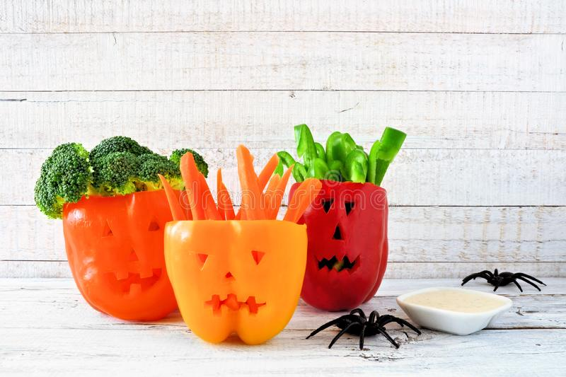Halloween vegetables and dip in Jack o Lantern peppers on white wood royalty free stock images