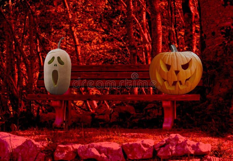 Halloween-viering twee enge en griezelige gesneden pompoenen op een parkbank in een verschrikkings boslandschap royalty-vrije stock fotografie