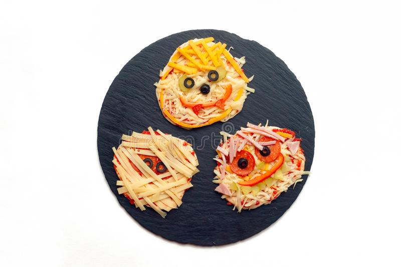 Halloween-voedselidee - eigengemaakte pizza, Minidiepizza's met spinnen en brijen voor Halloween worden verfraaid stock afbeeldingen