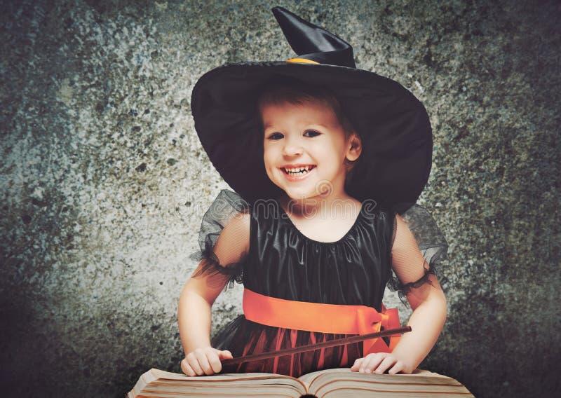 Halloween vrolijk weinig heks met toverstokje en boek conjur stock fotografie
