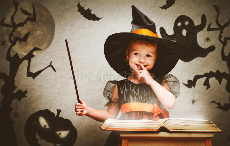 Halloween vrolijk weinig heks met toverstokje en boek conjur stock foto's