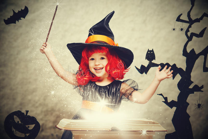 Halloween vrolijk weinig heks met toverstokje en boek conjur stock foto