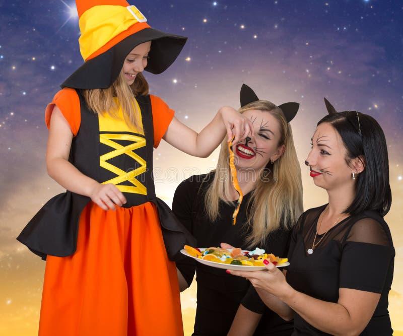 Halloween Vrouw twee bij kostuums zwarte katten wordt behandeld aan de kleine heks met suikergoed Mooi meisje in Halloween-kostuu royalty-vrije stock foto