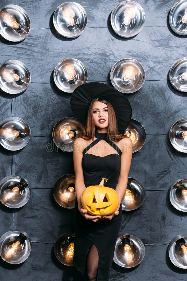 Young blonde woman holding pumpkins for halloween stock photos