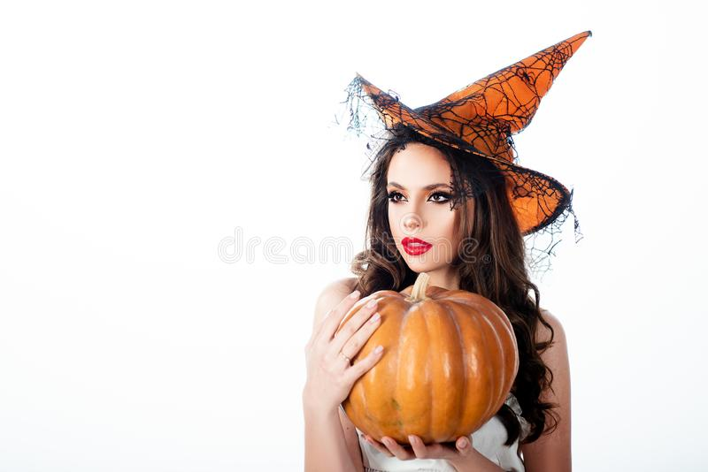 Halloween Witch with a carved Pumpkin - isolated on white background. Emotional young woman in Halloween costume stock image