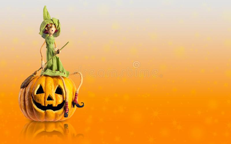 Halloween Witch and carved Pumpkin with magic lights. Copy space mock up royalty free stock photo
