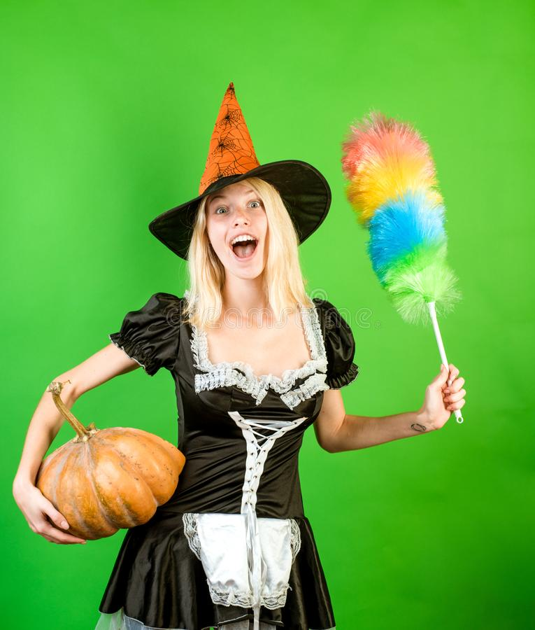 Halloween Witch with a carved Pumpkin and magic lights in green room. Emotional young woman in halloween costume on royalty free stock image