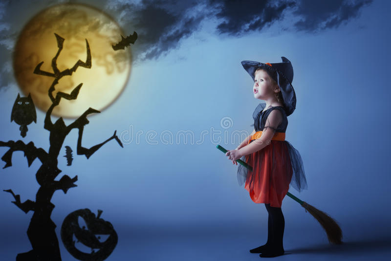 Halloween. Witch child flying on broomstick at sunset night sky. stock images