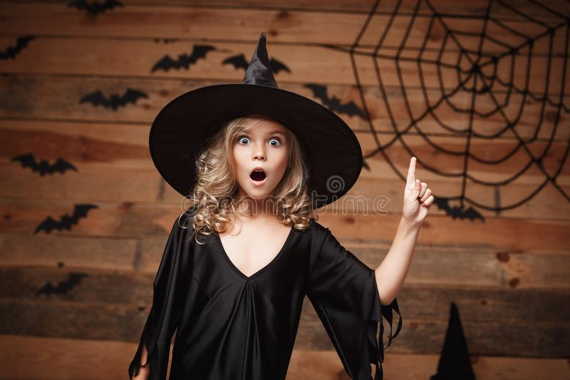 Halloween Witch concept - closeup shot of little caucasian witch child shocking face posing with bat and spider web on wooden stud. Io background royalty free stock photo