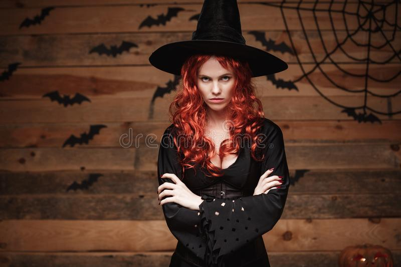 Halloween witch concept - Halloween red hair Witch holding arms posing with angry face over old wooden studio background. stock images