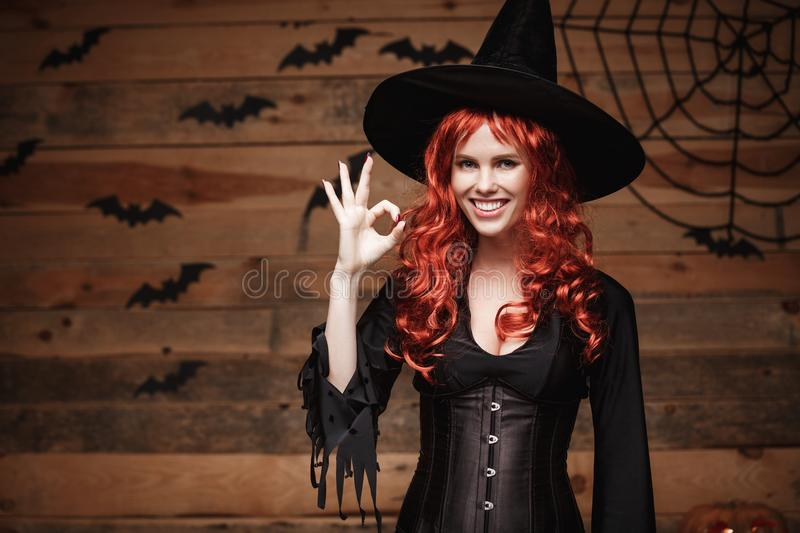Halloween witch concept - Happy Halloween red hair Witch holding ok sign with fingers posing over old wooden studio background. stock photos