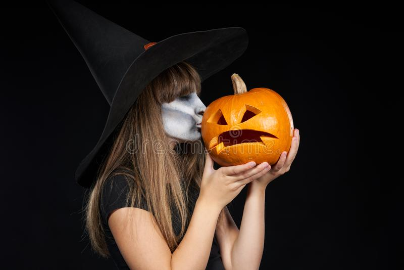 Halloween witch girl giving a kiss to Jack-O-Lantern pumpkin royalty free stock photography