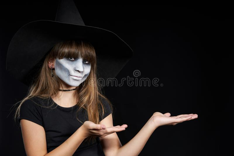 Halloween witch girl looking at camera showing blank copy space on her palms stock images