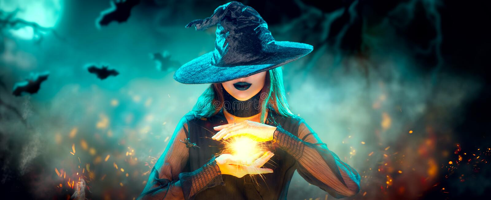 Halloween Witch girl with making witchcraft, magic in her hands, spells. Beautiful young woman in witches hat conjuring. Spooky dark magic forest background royalty free stock photo