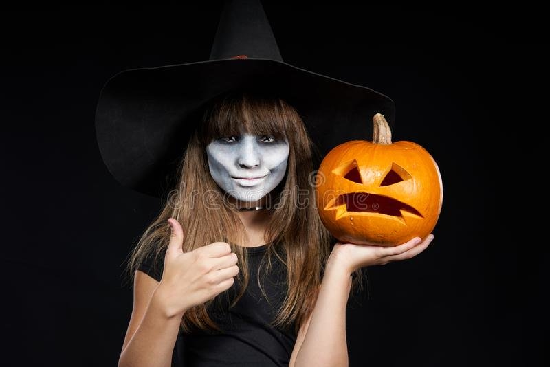 Halloween witch girl showing Jack-O-Lantern pumpkin on palm royalty free stock photography