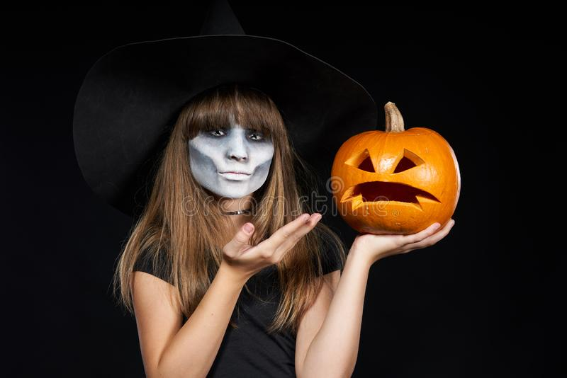 Halloween witch girl showing Jack-O-Lantern pumpkin on palm royalty free stock images