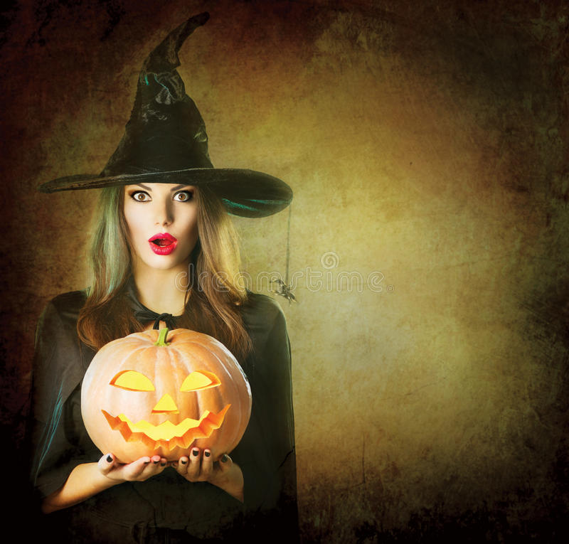 Halloween Witch holding carved pumpkin Jack Lantern. Halloween Witch holding carved Jack lantern pumpkin royalty free stock photography